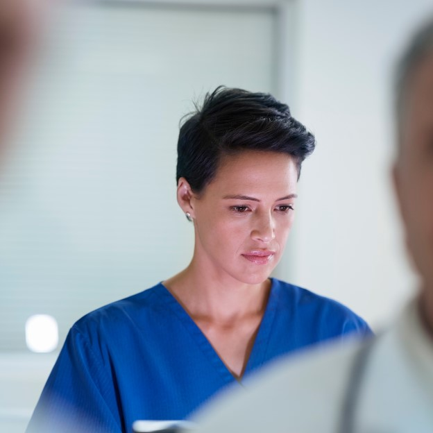 Female doctor wearing blue scrubs looking at computer with other doctors in the room