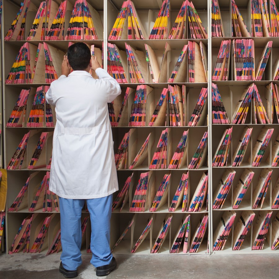 medical professional sorting through shelves of patient files.