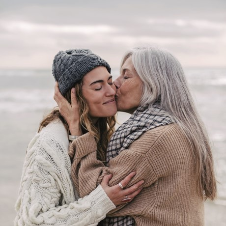 Two women, one older and one younger, embracing each other on a beach.